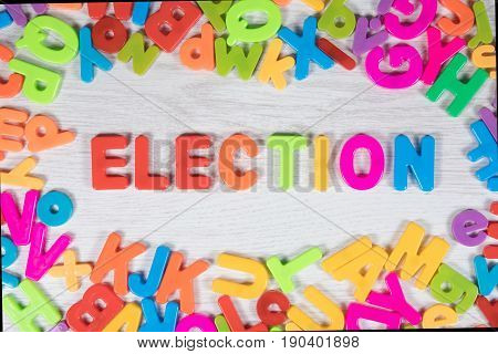 Brightly colored magnet letters create border around the word election on a white background