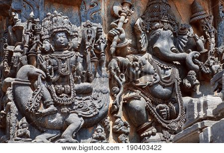 Ancient relief with Lord Brahma on swan and Ganesh the Hindu temple walls with patterns, vedic and puranic scenes, mythical beasts and gods. 12th century Hoysaleshwara temple in Halebidu, India