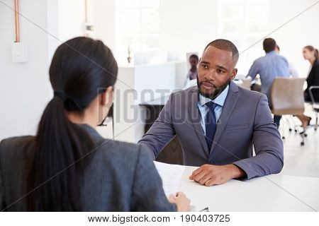Businessman and woman sitting at desk in an open plan office