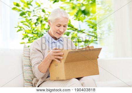 delivery, shipping and people concept - happy smiling senior woman looking into open parcel box at home over window and green natural background