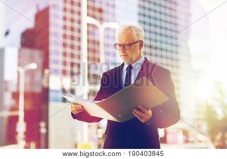 business, office work and people and concept - senior businessman paging documents in ring binder folder on city street