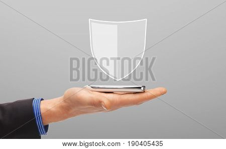 business, people and cyber protection concept - close up of male hand with virtual antivirus program shield icon above smartphone over gray background