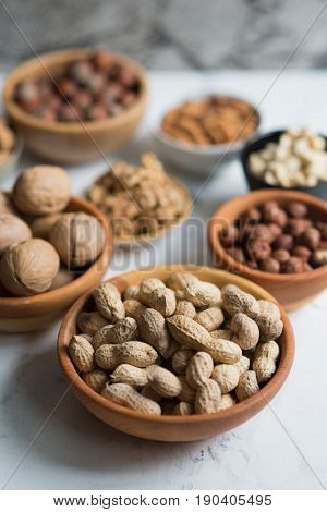Assorted nuts in wooden bowls, peanuts in focus