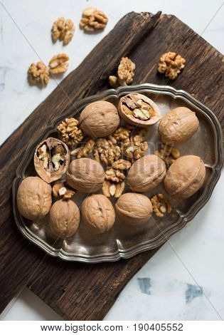 Walnuts in cracked shell on silver tray on wooden surface
