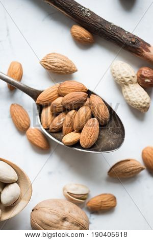 Almond nuts in big spoon over white surface