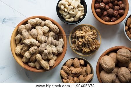 Assorted nuts in bowls on white surface, view from above. Peanuts, almond, walnut, cashew and hazelnuts
