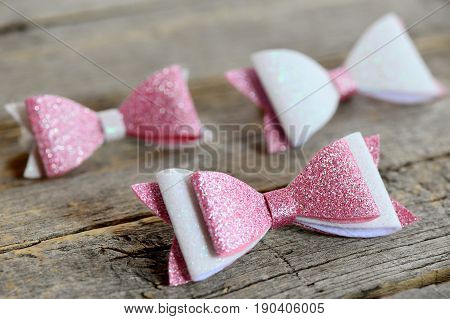 Lovely beautiful bows for hair. Pink and white shiny felt bows for girls. Beautiful hair accessories set on a wooden table
