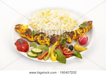 Grilled marinated morsels of chicken without bones arranged on a plain white plate. Fusion food concept. Called chelo joojeh or jujeh kebab in Persian cuisine. Closeup studio shot on white tabletop.