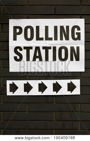 Polling Station sign on black brick wall in London, UK, with arrows pointing the way in to vote.