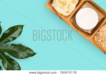 spa, bodycare and natural cosmetics concept - soap with himalayan pink salt and scrub in wooden bowl with green leaf on turquoise background