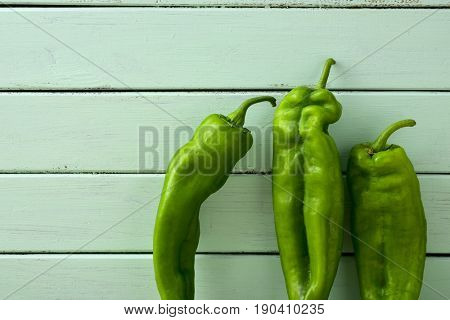 some raw green peppers on a rustic wooden table, against a pale green background, with a blank space