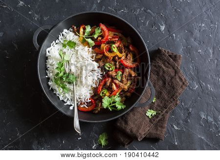 Spicy beef with vegetables and rice in a cast iron skillet on a dark background top view. Asian style food