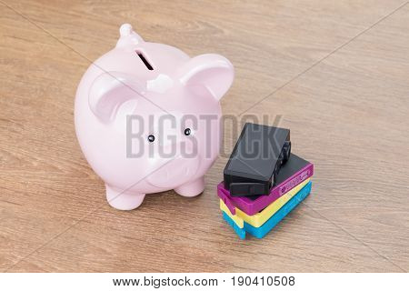 Piggy Bank Next To Printer Cartridges