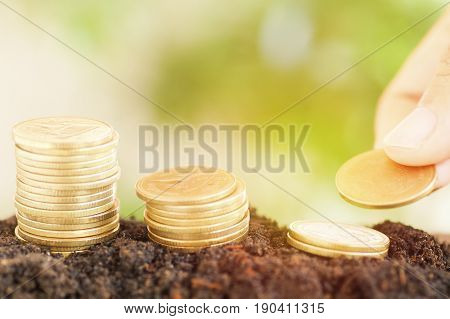 saving money preset by Male hand putting money coin growing up concept in business finance and account bank