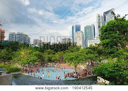 Kuala Lumpur, Malaysia - February 10 2016: KLCC Park is a public park in Kuala Lumpur Malaysia. Wading pool is in the middle of the park in front of Suria KLCC mall and Petronas  Towers