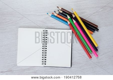 Creativity art or primary learning concept with a bundle of colorful pencil crayons lying alongside a double page open notebook with copy space in an overhead view