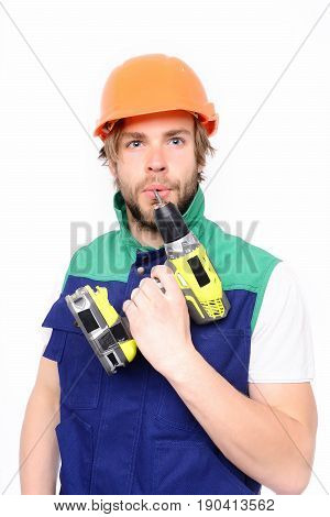 Contractor and tool. Yellow electric screwdriver in hand of concentrated and thoughtful builder isolated on white background. Concept of finished work and professional skills