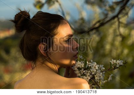Woman With Hair Bun Posing With White, Blossoming Flowers