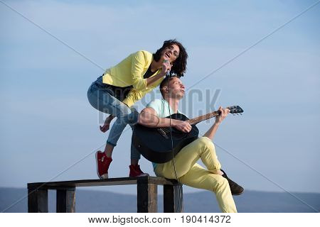 Romantic couple of musicians performing on table on blue sky. Adorable woman singer or girl singing to mic and handsome man guitarist playing guitar on sunny summer day. Music concert performance