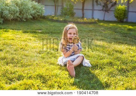 Funny child with candy lollipop, happy little girl eating big sugar lollipop, kid eat sweets. surprised child with candy. isolated on bright background, studio. Beautiful little girl with lollipop