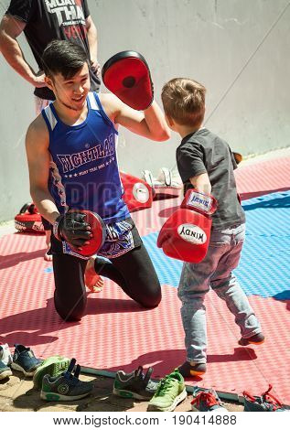 Khabarovsk Russia - May 20 2017: Young Asian boxer training a small kid in Muay Thai. Little boy in boxing gloves exercising with a trainer in a gym working on punch movements.