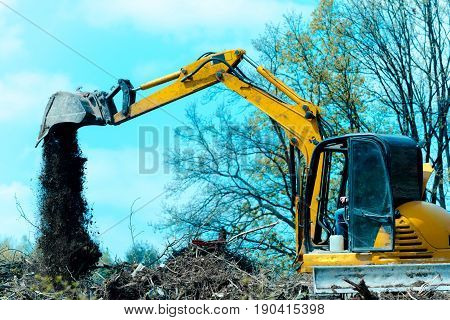 Digger or excavator machine with yellow shovel unloading ground and dust at construction site outdoors on blue sky background. Earthmoving works. Building machinery. Equipment and engineering