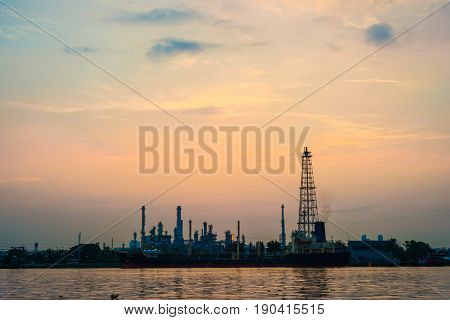 Oil Refinery Petrochemical Industry With River Sunrise