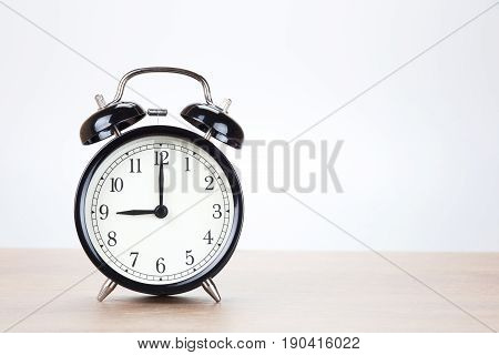 Old-fashioned round black alarm clock with two bells standing on a wooden table facing the camera with lateral copy space