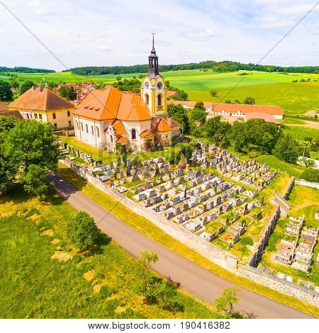 Church of St John the Baptist (1358) with graveyard in small village Vreskovice. Architecture from above. Religious monument in Czech Republic, Central Europe.