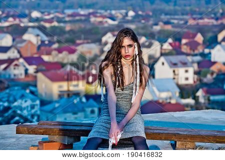 girl woman or model with stylish makeup and white strings in long brunette hair hairstyle in grey dress sitting on wooden bench outdoors on rural environment. Summer vacation
