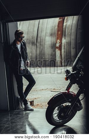 Stylish Young Man In Sunglasses And Leather Jacket Standing In Garage And Looking At Motorcycle