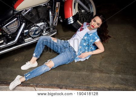 Sensual Stylish Young Woman In Denim Vest Lying On Pavement Curb Near Motorbike