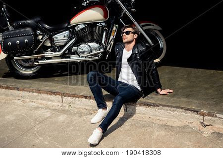 Handsome Stylish Young Man In Leather Jacket And Sunglasses Sitting On Concrete Curb Near Motorbike