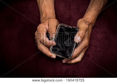 An elderly man holds an empty purse. The concept of poverty in retirement .
