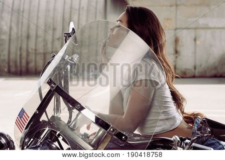 young woman sitting on motorcycle and looking into rear-view mirror