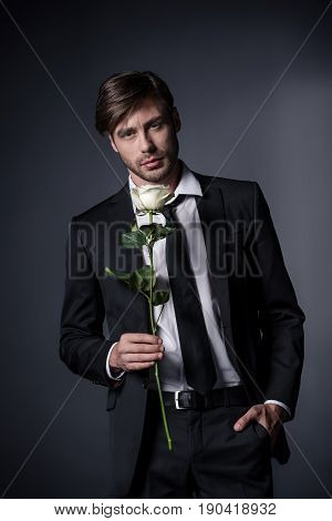Portrait Of Stylish Man In Suit Holding White Rose And Looking At Camera Isolated On Black
