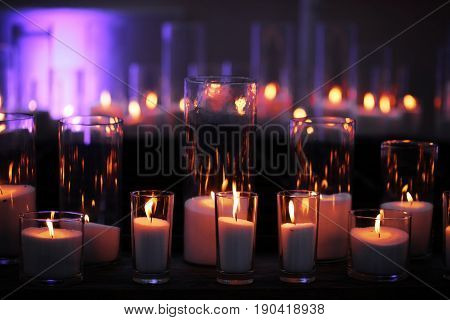 wax candles burning in stylish glass candleholders with flame reflection on dark wooden board on blurred background. Home decor. Holidays celebration. Heat energy