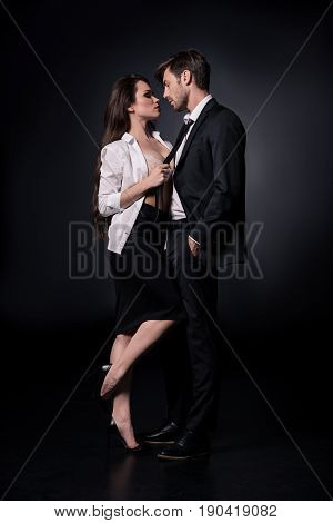 Young Sexy Woman Seducing Young Man In Suit Isolated On Black