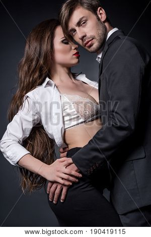 Young Passionate Couple In Love Embracing And Able To Kiss Isolated On Black