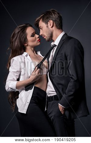 Passionate Girl Seducing Young Man In Formal Wear Isolated On Black