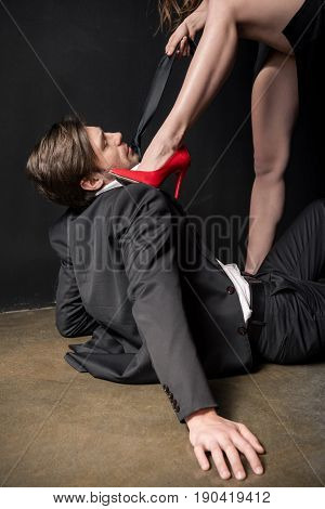 girl in red stilettos dominating on young elegant man in sexual scene