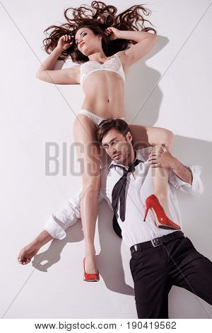 Young Woman In White Lingerie Lying On The Floor With Elegant Man In Sexual Scene
