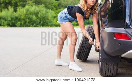Woman changes the wheel of car on a road.
