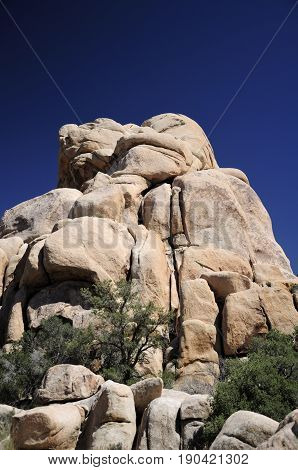 Rock formations within the arid desert ecosystem on the Hidden Valley Trail within Joshua Tree national Park in Joshua Tree California.