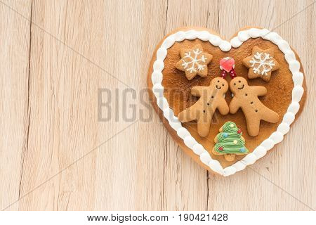 Gingerbread heart decorated with Gingerbread Men Gingerbread Stars and a Christmas Tree Cookie on light brow wooden background with lots of copy space.
