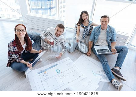 Feeling comfortable. Team of positive nice young architects sitting on the floor and looking at you while working together in the informal atmosphere