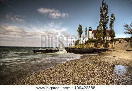 Lighthouse And Crashing Waves. The Point Betsie Lighthouse on the rocky coast of Lake Michigan with waves crashing on the shore. Benzie County, Michigan