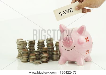 hand holding lons sign over money coins and piggy bank isolated on white background