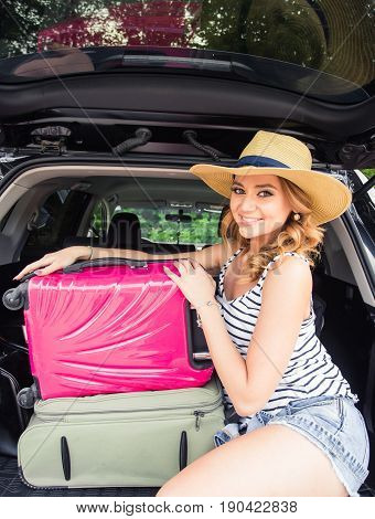 Pretty woman portrait at the car trunk with suitcases.
