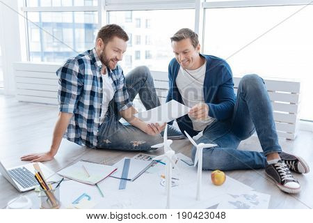 Environmental protection. Positive nice male environmentalists looking at the windmill drawing and discussing it while thinking about the planet